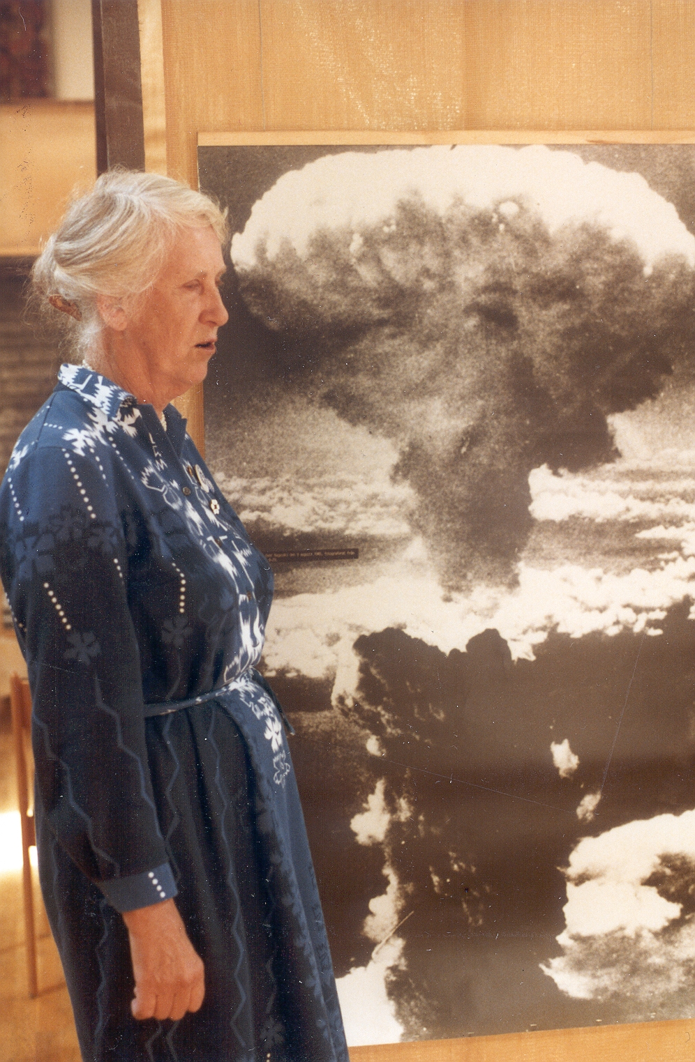 Kerstin Anér in front of an image of a nuclear detonation. Photographer and date unknown (KvinnSam, Gothenburg University Library, B36)