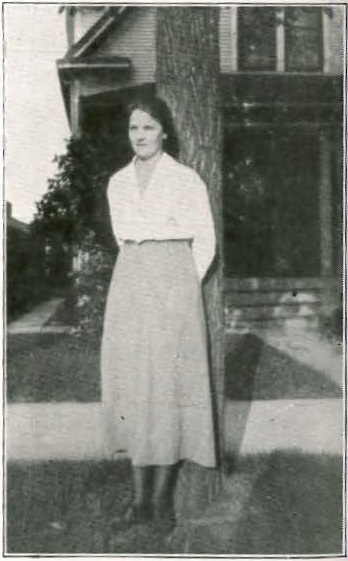 Signe Aurell in front of her house, 1919. Image published in Bokstugan 1:8, 1920. Photographer unknown