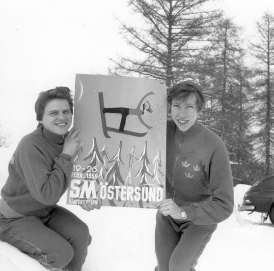 Sonja Edström (left) and Irma Johansson hold up a poster for the Swedish Cross-Country Skiing Championships in  Östersund, 1956. Photo: Hallings foto/Östersunds-Posten (Jamtli Bildbyrå, Hlg13782)