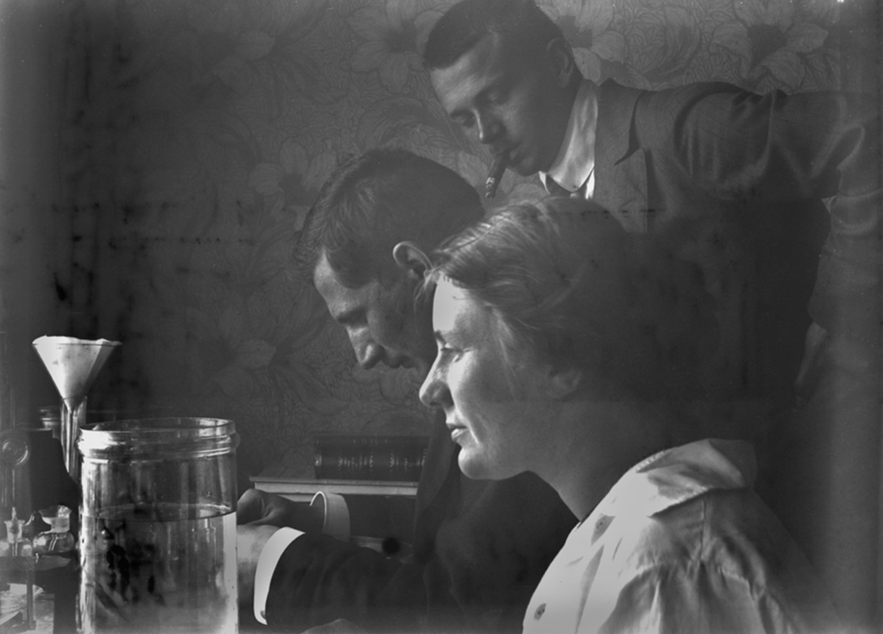 Elisabet Petersson vid arbetsbord med två icke namngivna män, Helgoland, 1913. Fotograf okänd, eventuellt självporträtt (Göteborgs naturhistoriska museums arkiv)