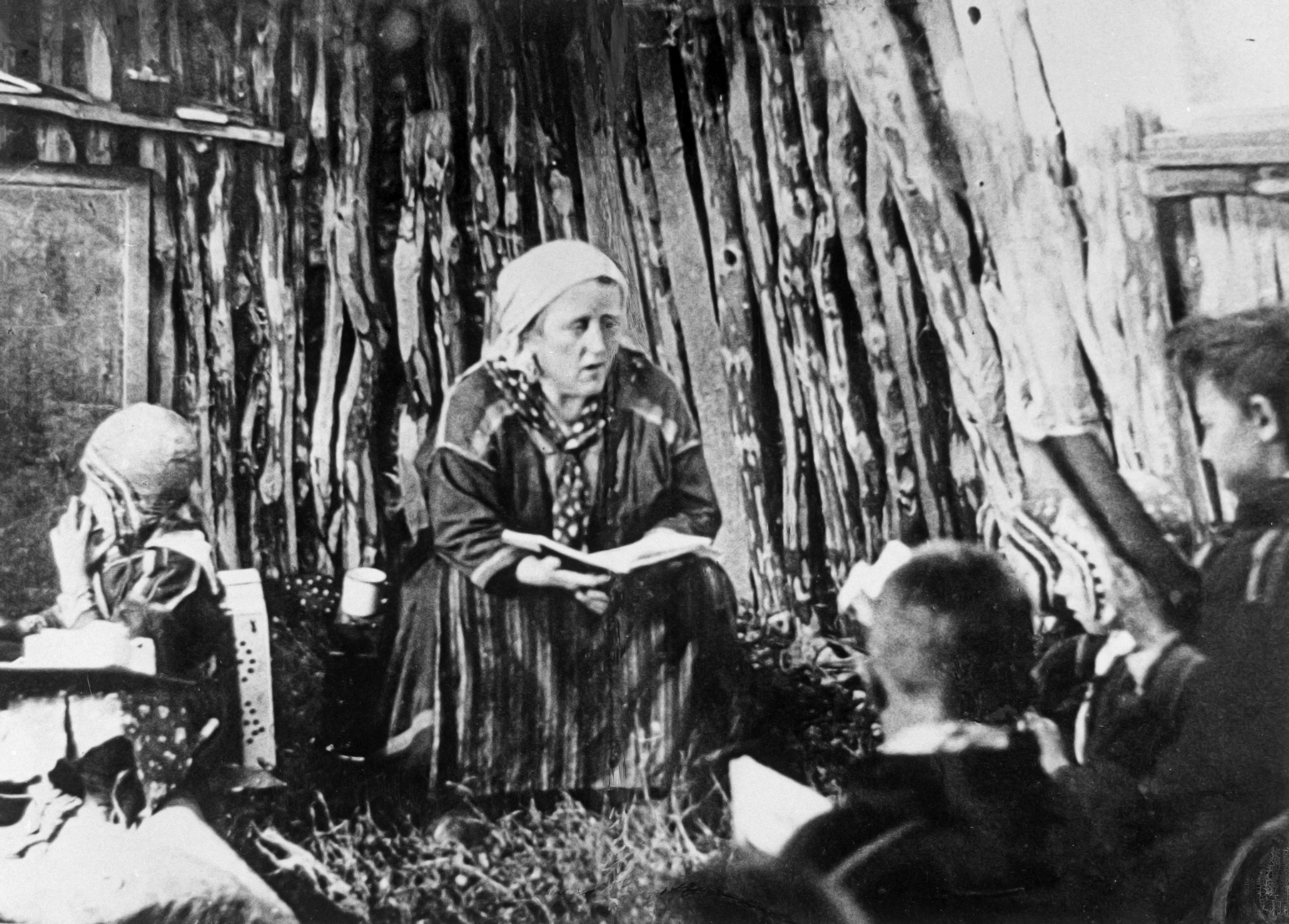 Teres Torgrim håller lektion i skolkåtan i Maajärvi, Jukkasjärvi socken. Fotograf och år okänt (Norrbottens museums bildarkiv)
