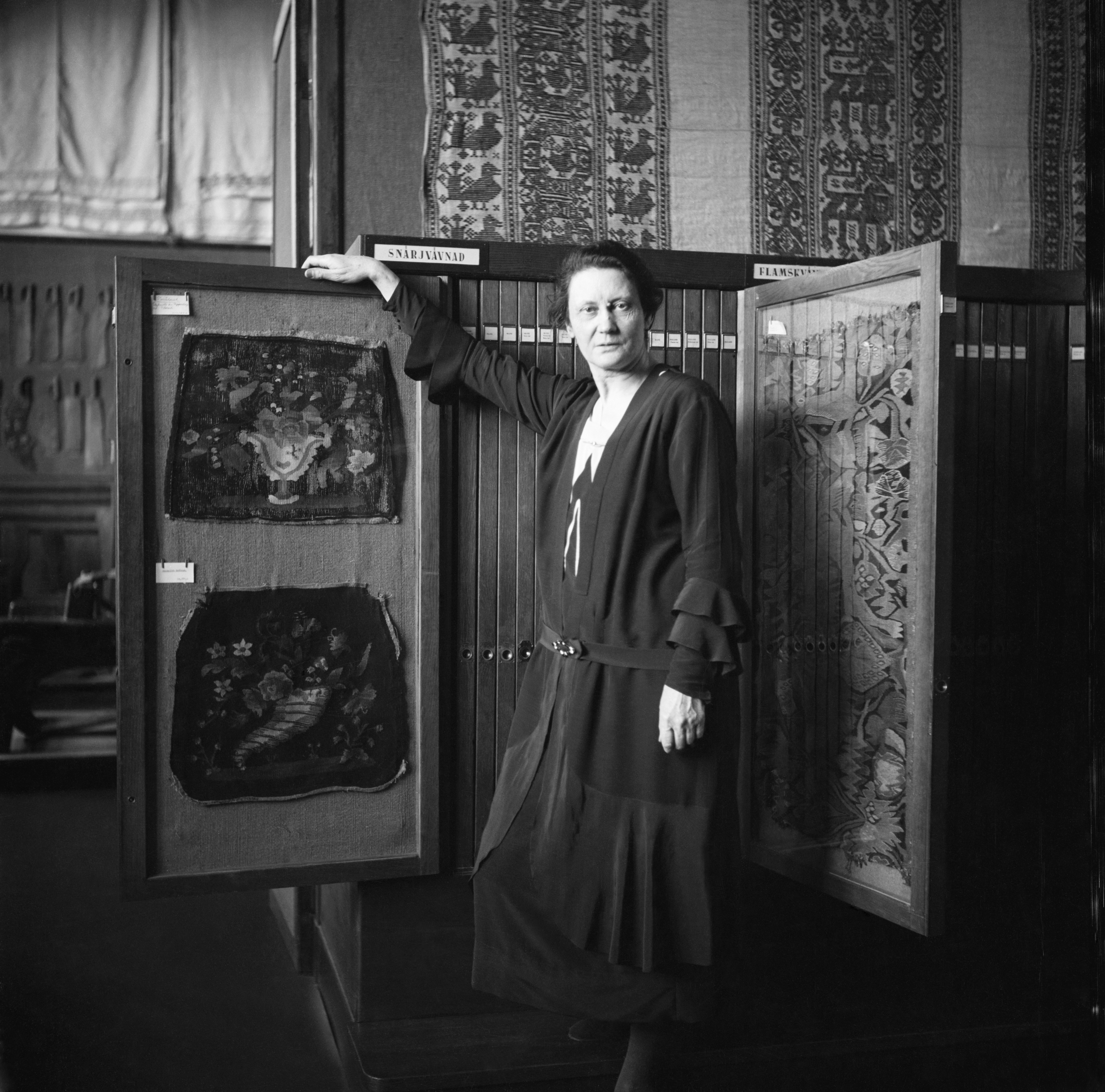 Emelie von Walterstorff with samples from the textile collection at Nordiska museet. Photographer and year unknown. Nordiska museet (NMA.0058669)
